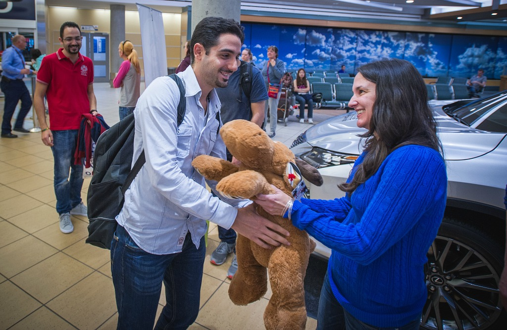 Syrian student Aref Sayegh receives a stuffed moose from UAlberta volunteer Michelle Garcia Vega as a welcome to Canada and the university. (Photo: UAI)