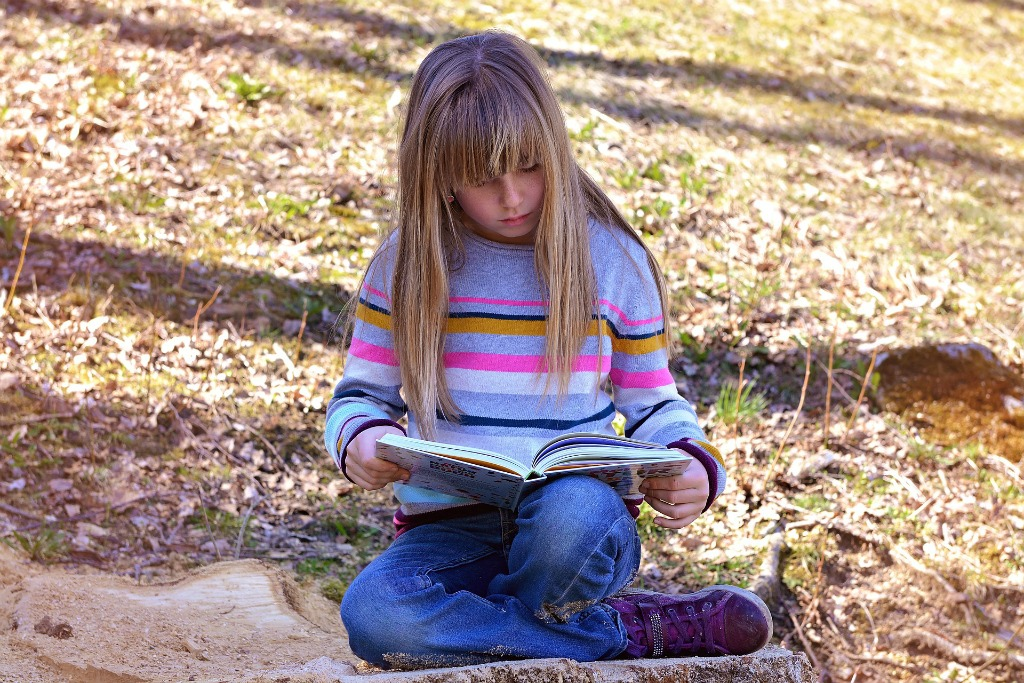 A young girl reads a book outdoors.