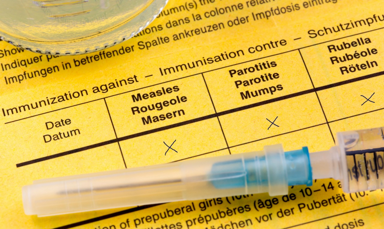 An MMR (measles, mumps, rubella) vaccination needle lying on top of immunization papers