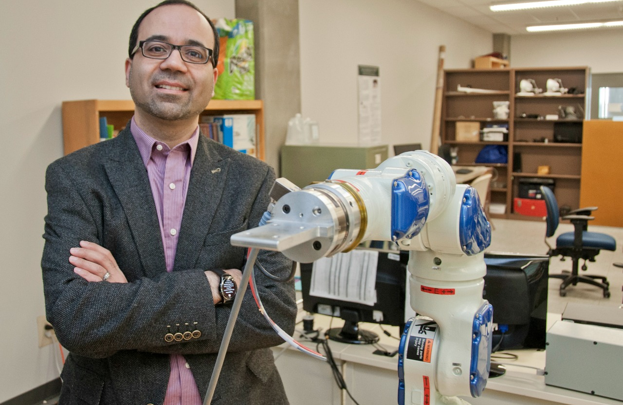 Mahdi Tavakoli with a robotic arm in his lab.