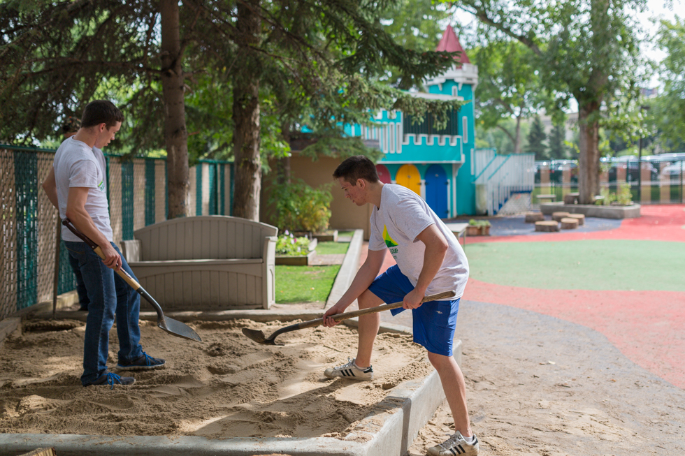 Students shovel new sand into a sandbox at the daycare playground in HUB Mall.