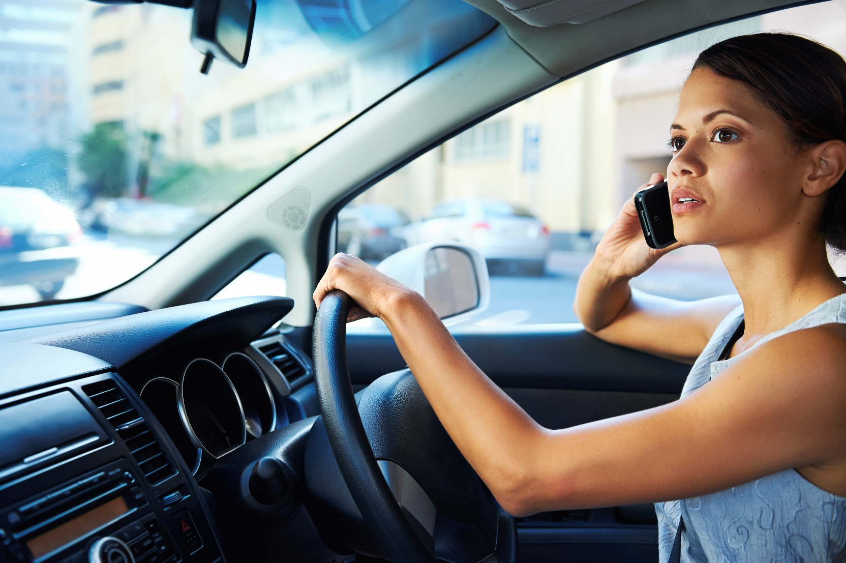 Stock image of a woman talking on a cell phone while driving