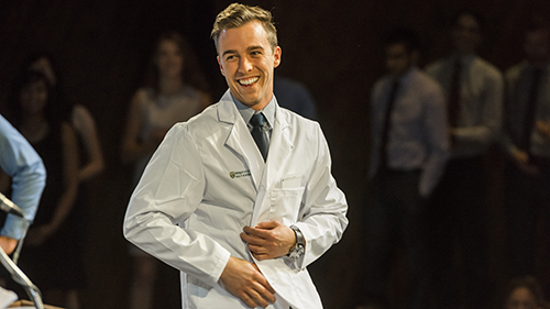 Dr. D. Douglas Miller shakes the hand of an MD student at the 2014 White Coat Ceremony