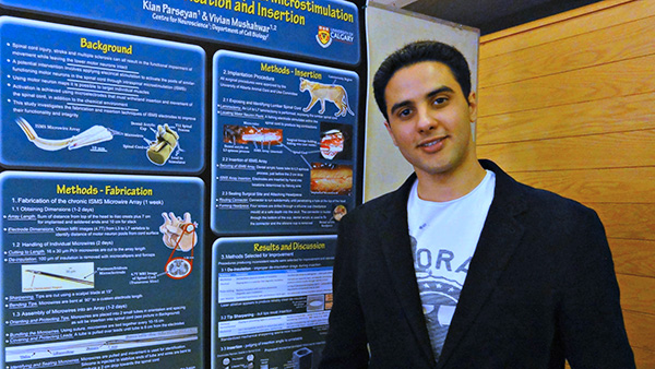 A graduate students with his research poster