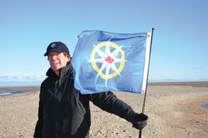 John Geiger holding the flag of the Royal Canadian Geographical Society on the RGS Islands in the Summer of 2012