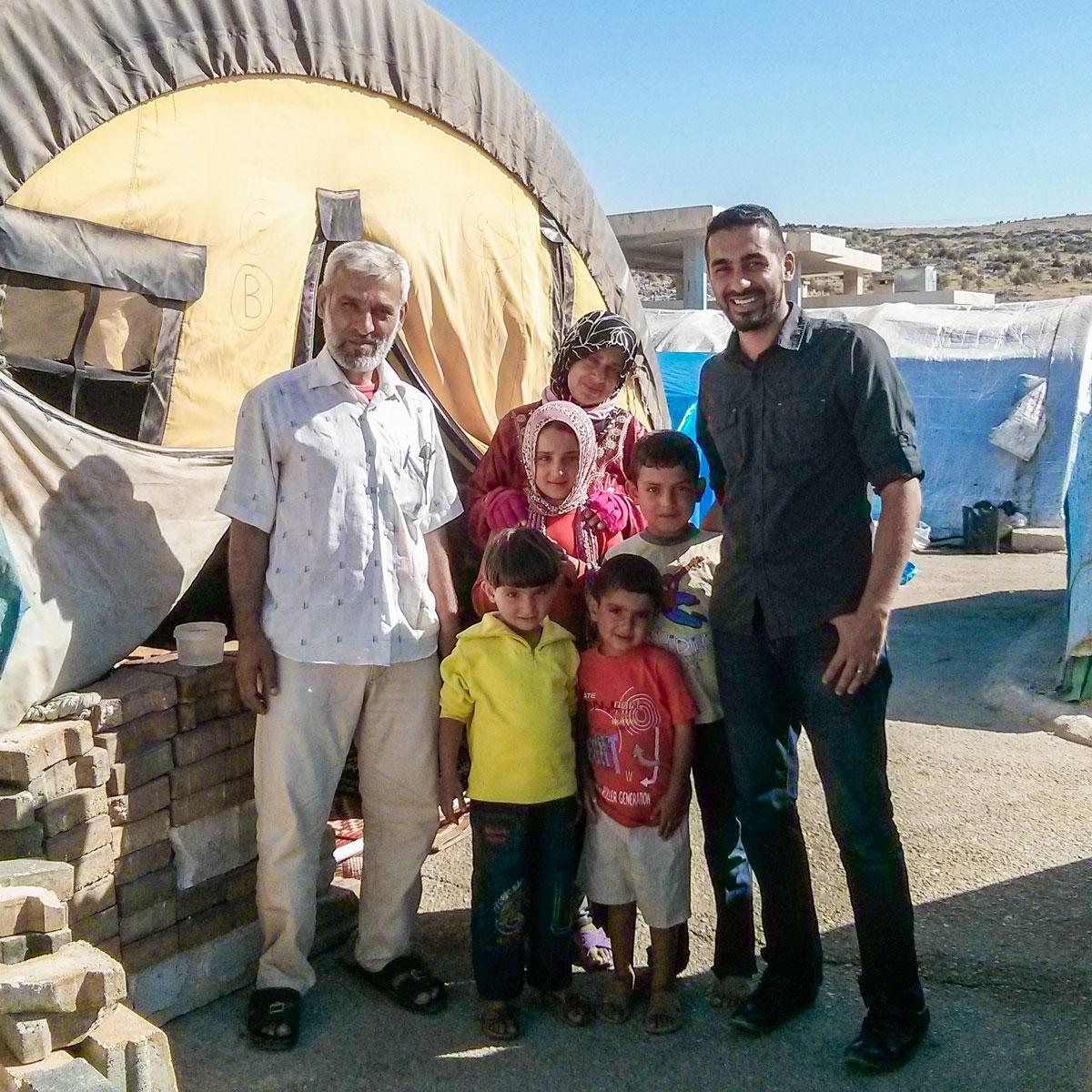 Saleem Al-Nuaimi Standing with Refugee Family
