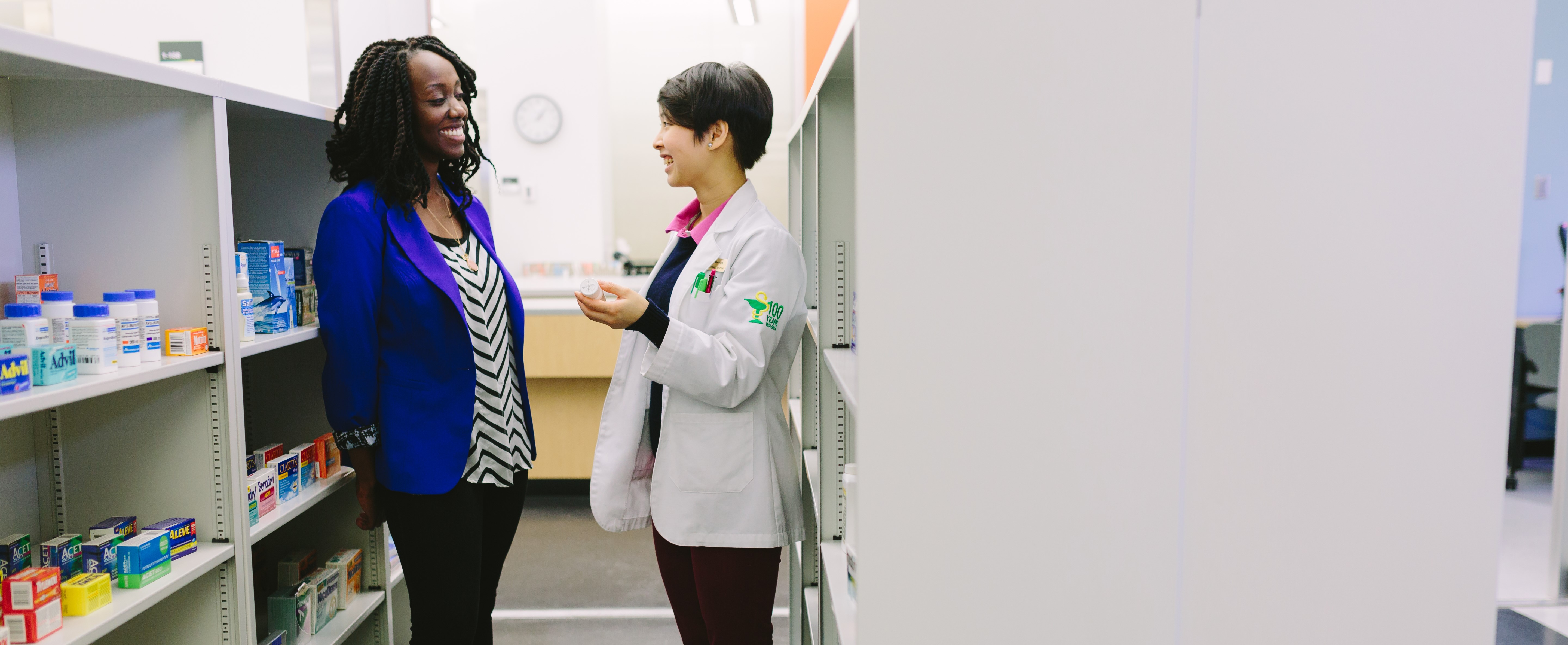 Community pharmacist assisting a female patient in the aisle of a community pharmacy.