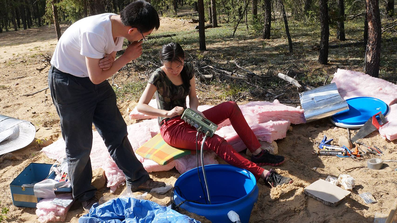 Associate professor Jeff Gu and graduate student Ruijia Wang work on a seismic station in the field.