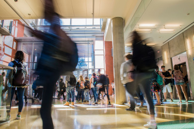 A delayed exposure photo showing students moving through the CCIS building at UAlberta during a class change.
