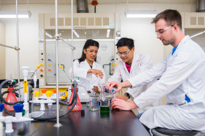 Three students working with beakers in a chemistry lab at UAlberta.