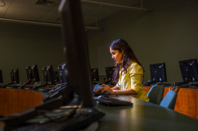 A student coding on her computer in an empty computer lab.
