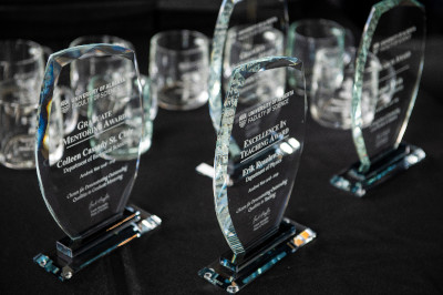 A black table of glass plaques and awards celebrating excellence in teaching science at UAlberta.