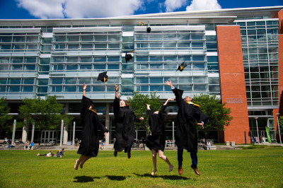 Four science students in their graduation regalia jump and throw their caps in front of UAlberta's CCIS building.
