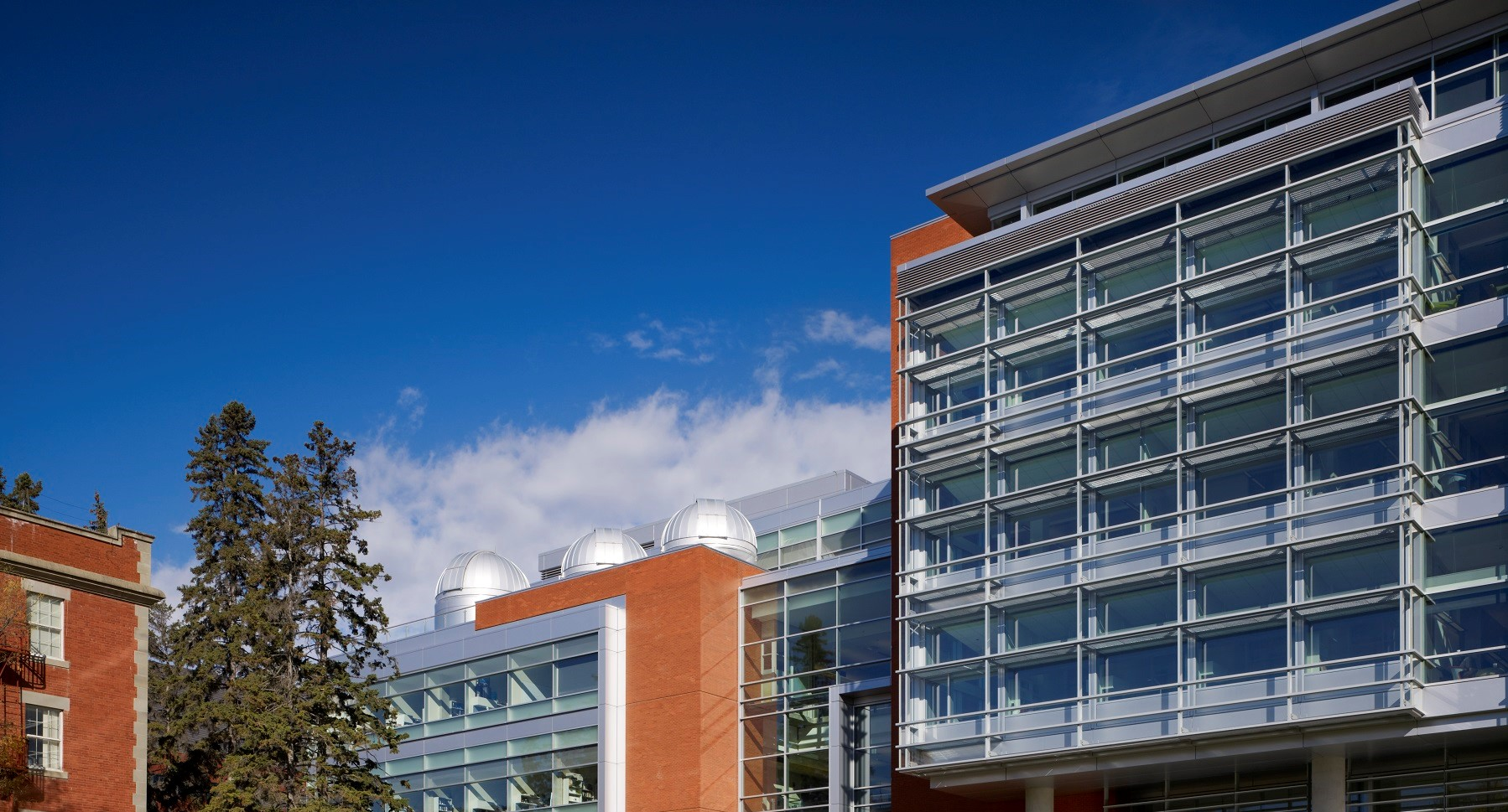 The Faculty of Science's CCIS building in the daytime with students walking through the Quad.