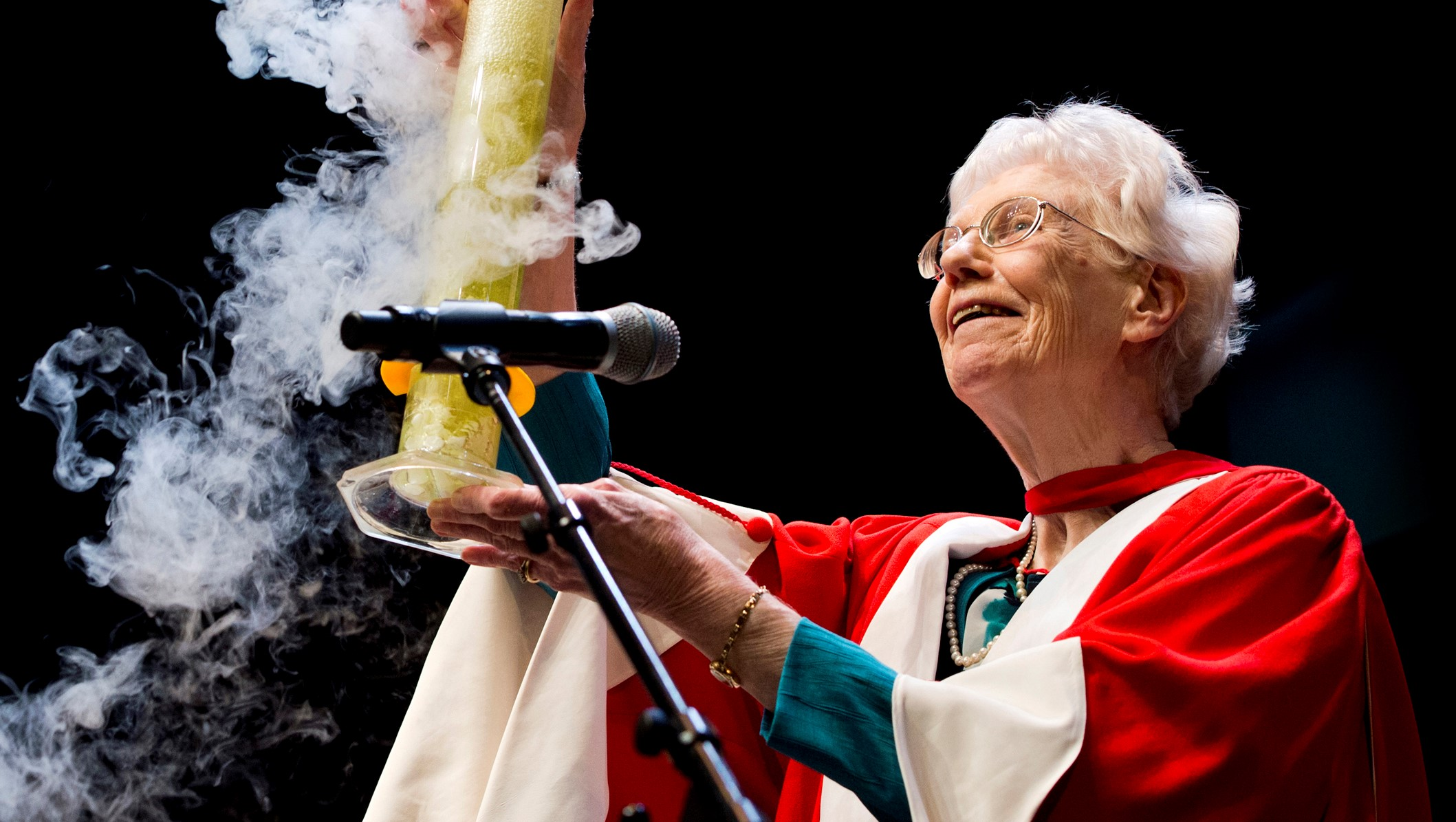 Margaret-Ann Armour holding a bubbling beaker aloft at a convocation ceremony